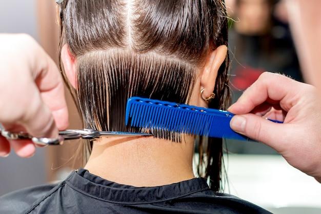 美容師の手は、女性のクローズアップと背面図の髪をカットします。