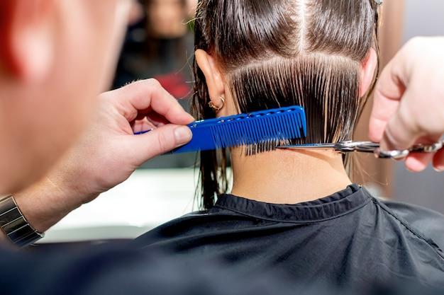美容師の手は、女性の髪をクローズ アップし、後ろ姿をカットします。