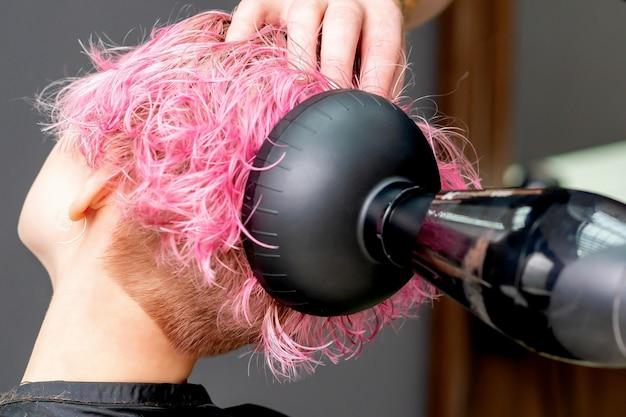 Руки парикмахера сушат розовые волосы крупным планом женщины.