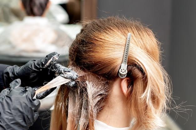 Руки парикмахера в черных перчатках красят волосы женщины. окрашивание волос.