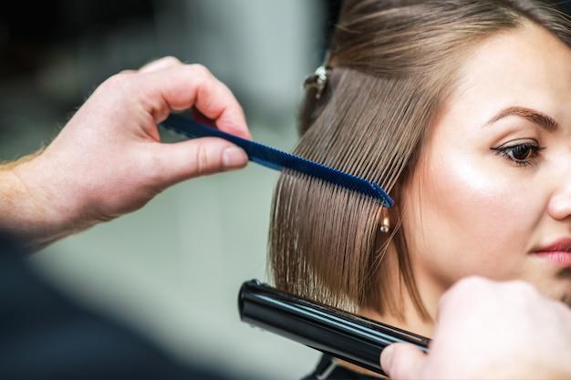 茶色の髪を矯正する美容師の手。