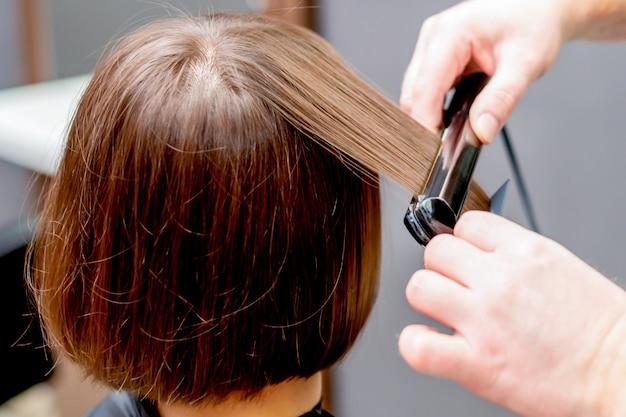女性の髪を整える美容師の手。