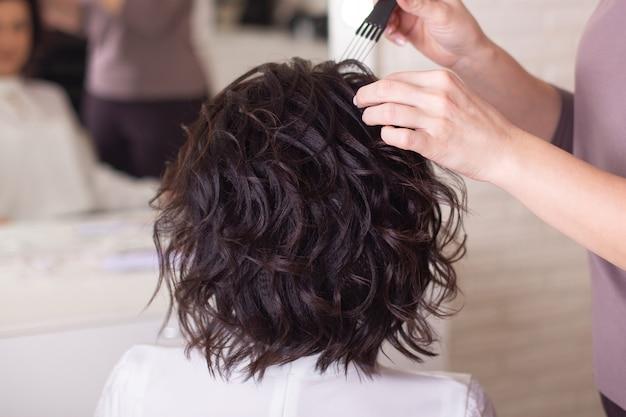 Руки парикмахера и спина брюнетки
