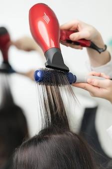 미용사의 손은 빨간색 헤어드라이어와 파란색 빗을 사용하여 고객의 긴 갈색 머리를 말립니다.