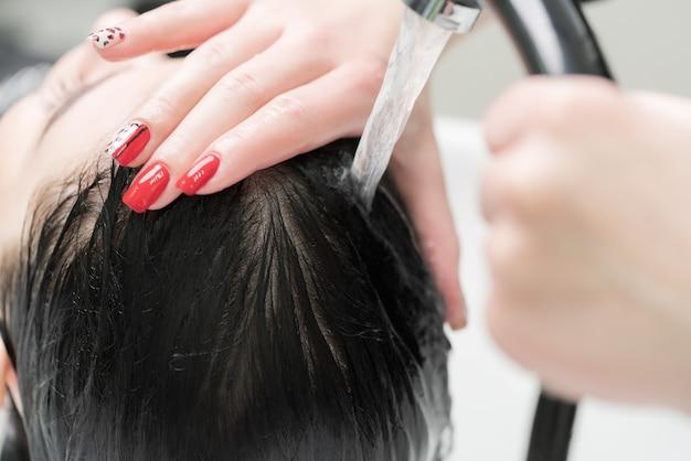 미용사의 손은 미용실에서 샴푸를 하기 위해 특별한 전문 세면대에서 샴푸로 갈색 머리 여성의 긴 머리를 씻습니다.