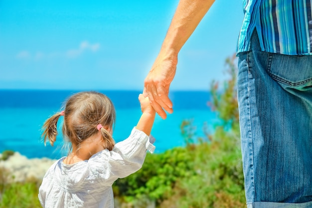 Руки счастливого родителя и ребенка на берегу моря