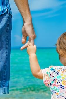 Руки счастливых родителей и детей на фоне моря греции