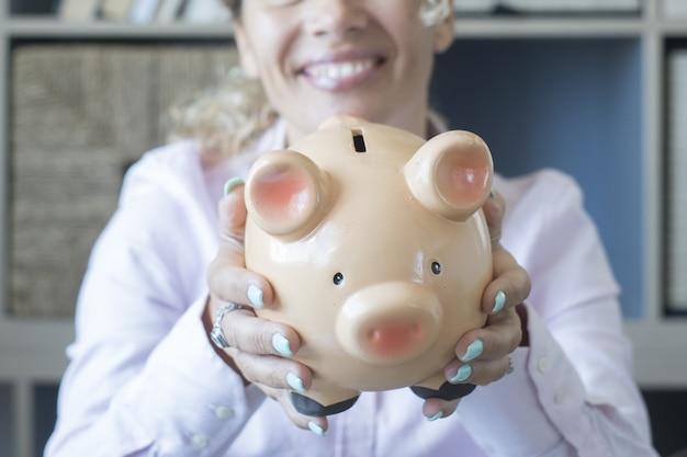 お金を節約するために貯金箱を示す幸せな女性の手。休暇や将来の計画のためにお金を節約するという概念。彼女の夢を実現するためにお金を節約するために貯金箱を持っている女性