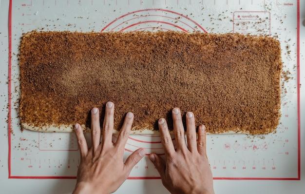 Руки испанского пекаря готовят булочки с корицей.