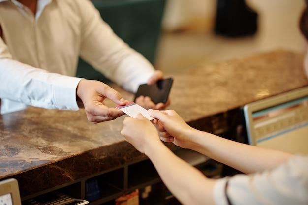 ゲストにデジタルルームキーを与えるホテルの受付マネージャーの手