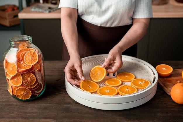 キッチンで冬の柑橘類の砂糖漬けの果物を作りながら、食品乾燥機のプラスチックトレイにオレンジスライスを置く主婦の手