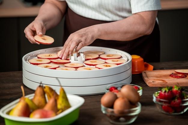 Руки домохозяйки кладут дольки красных яблок на пластиковый поднос домашней сушилки для фруктов среди спелых груш, клубники и киви
