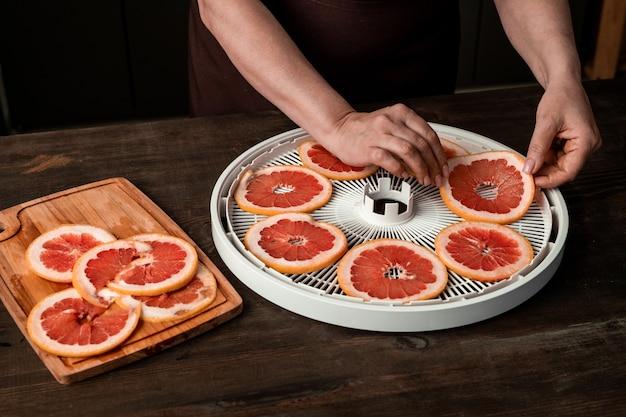 それらの写真を撮っている間テーブルの上に新鮮なスライスされたグレープフルーツとフルーツドライヤーの丸いトレイの上にスマートフォンを持つ主婦の手