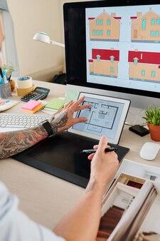 Руки дизайнера интерьера проверяют план строительства дома при работе с графическим планшетом за своим столом