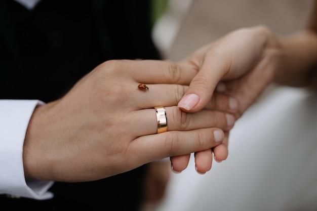 Руки молодоженов с обручальным кольцом и жучком