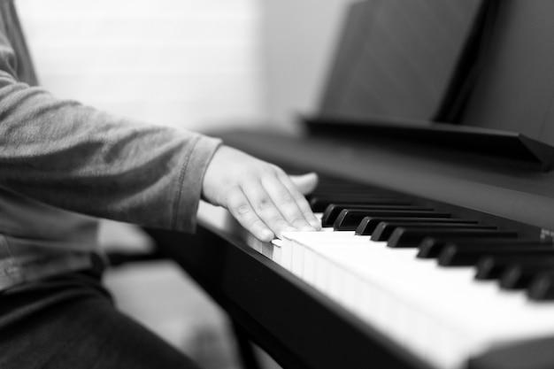 Руки ребенка, играющего на пианино. палец на белый ключ руки ребенка играть на пианино. нажатие пальцем на белый ключ