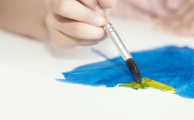 Руки маленькой азиатской девушки, рисующей абстрактную картину акварелью