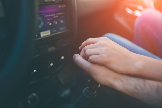 車の中で一緒に恋人の手がクローズアップ。彼が車を運転している間、男性の手に手をつないでエレガントな女性のクローズアップショット