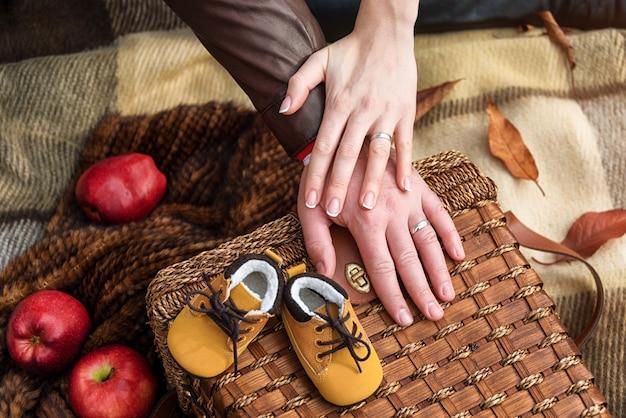 秋の公園、クローズアップでかわいい赤ちゃんの靴と愛情のあるカップルの手