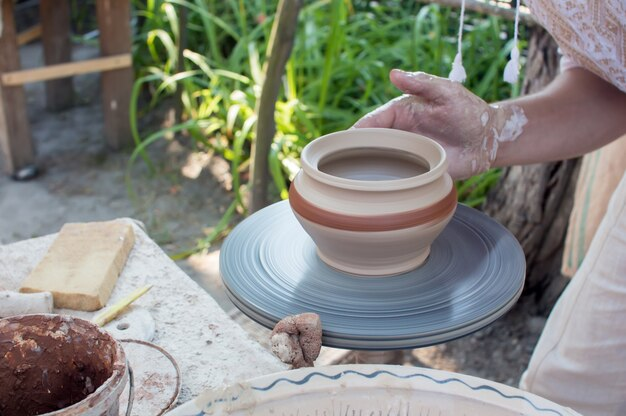 Руки лепки глиняного горшка на гончарном круге