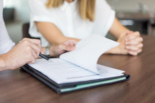 Руки мужчины исполнительной показывая контракт с женщиной-партнером на совещании.