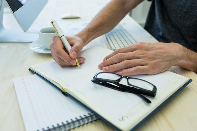 Руки мужского графического дизайнера писать на дневнике