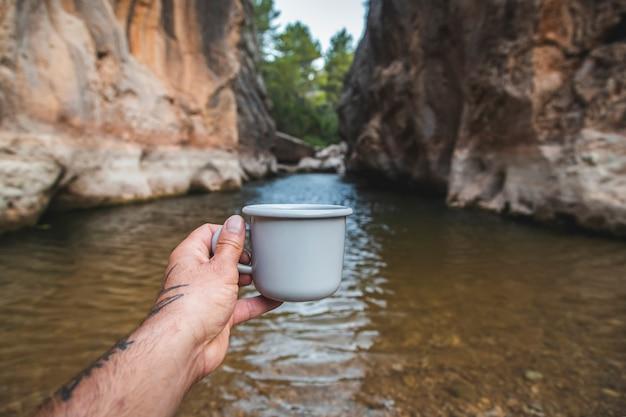 川岸に立って、温かい飲み物でマグカップを持っている男性観光客の手。