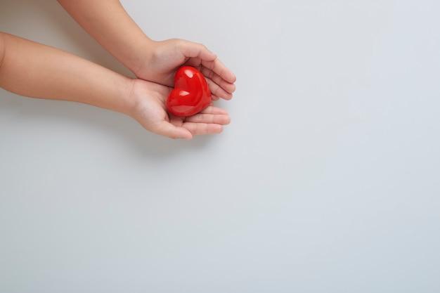 白い壁に赤いハートの男と子の手