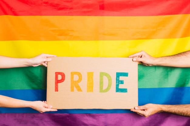後ろにゲイプライドの旗が付いた色で書かれたプライドという言葉で段ボールを持っている男性と女性の手