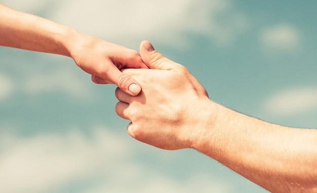 男性と女性の手が互いに手を伸ばし、サポートします。連帯、思いやり、そして慈善、救助。救いの手を差し伸べる。青空の背景に男と女の手。救いの手を貸す
