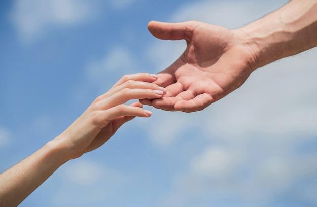 男性と女性の手が互いに手を伸ばし、サポートします。連帯、思いやり、そして慈善、救助。救いの手を差し伸べる。青空の背景に男と女の手。救いの手を貸す。