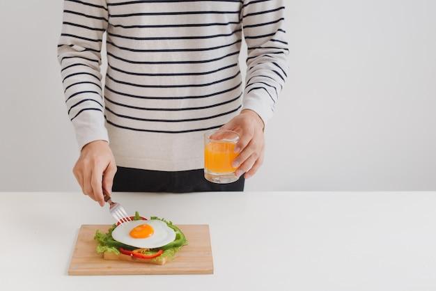 人間の手が紙に卵を切り、パン、ハーブ、ソーセージ、フレッシュジュースを添えます。