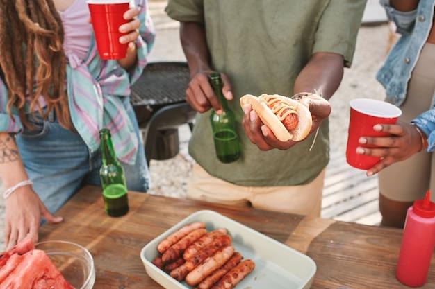 맥주를 마시고 해변 파티에서 친구들을 위해 핫도그를 만드는 남자의 손