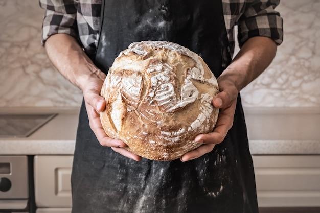 白パンの大きな塊を保持している男の手。小麦パンと家庭の台所で黒いエプロンの男性