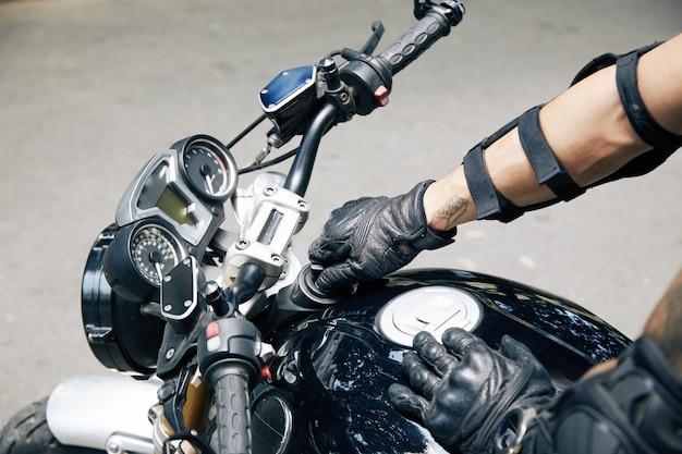 Руки человека в кожаных перчатках открывают бензобак своего мотоцикла