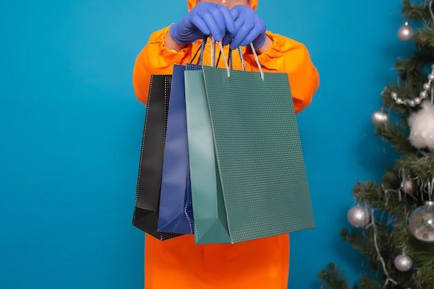 Руки человека держит три хозяйственные сумки