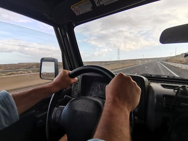 旅行中に道路で車を運転するハンドルの男の手。休暇中にロードトリップを楽しんでいる男。曇り空を背景に田舎道で車を運転する手
