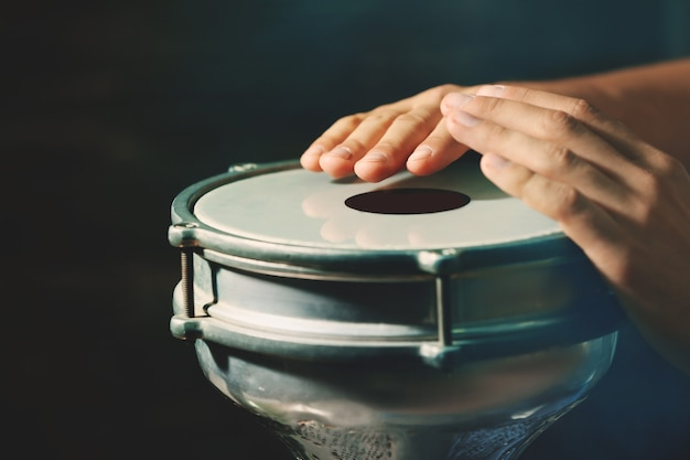 Руки человека, играющего на африканском барабане в темноте