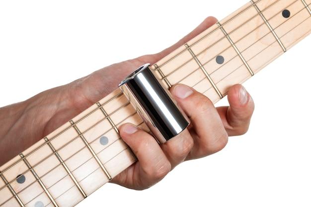 エレクトリックギターを弾く男の手。ギタリストの手。メープルのフレットボードのクローズアップで弦を押す金属製のスライダーを持つ指