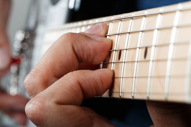 赤いピックのクローズアップでエレクトリックギターを弾く男の手