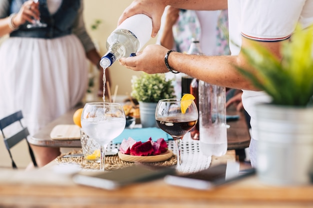 バックグラウンドで飲んでいる女性の間にランチテーブルでカクテルやさわやかな飲み物を準備するガラスにアルコールを注ぐ男の手。お祝いのための飲み物の準備