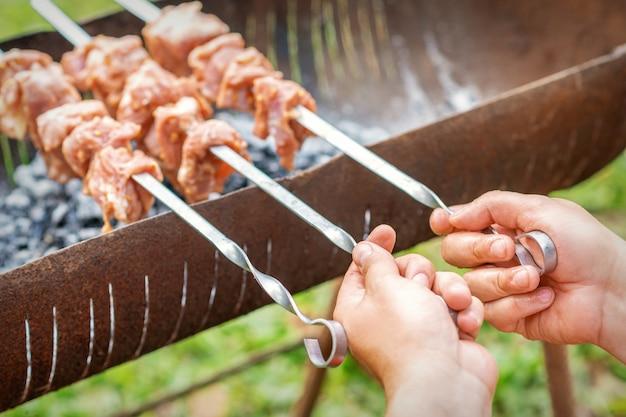 Руки человека готовит барбекю мясо