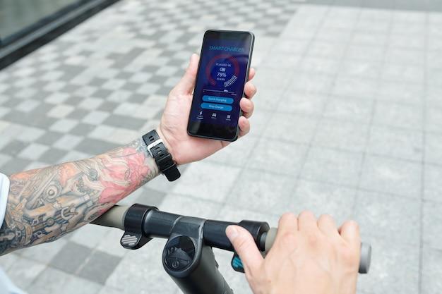電動スクーターに乗ってスマートフォンの画面でスマート充電器アプリケーションをチェックする男の手
