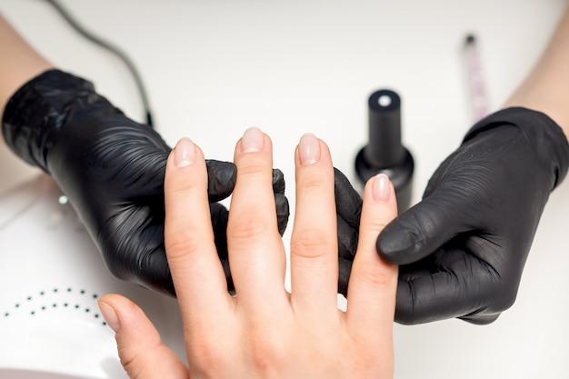 クライアントの指を保持しているネイリストの手