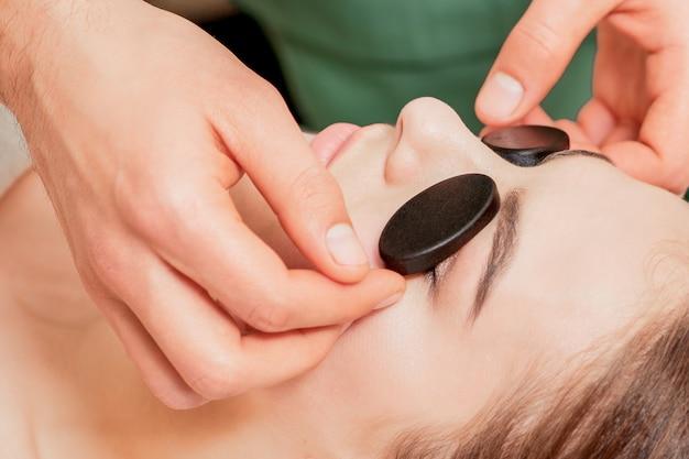 Руки массажиста кладут массажные камни на глаза молодой женщины во время расслабляющего массажа.
