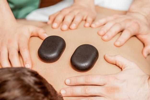 Руки массажистов, делающих массаж спины, в то время как горячие камни на спине человека закрываются в спа.