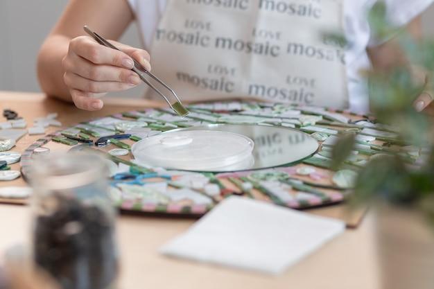 Руки мастера работают над новой современной красочной мозаикой. крупный план