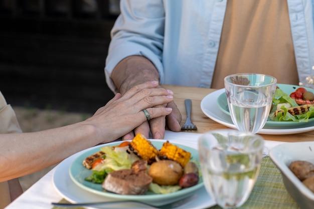 저녁 식사를 제공하는 테이블 옆에 앉아 있는 다정한 성숙한 부부의 손