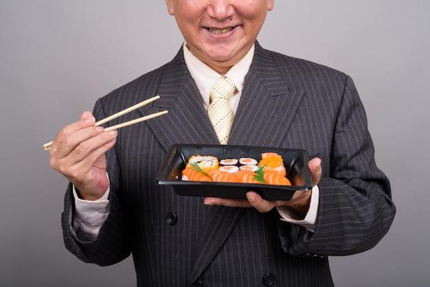 초밥을 들고 성숙한 아시아 실업가의 손에 gr에 대 한 롤