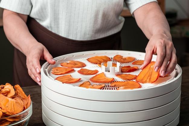 Руки зрелой женщины в фартуке берут сушеные ломтики хурмы или других фруктов с верхнего подноса домашней сушилки для пищевых продуктов на кухне